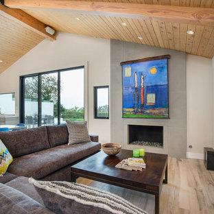 サンディエゴの大きいビーチスタイルのおしゃれなLDK (磁器タイルの床、グレーの床、グレーの壁、標準型暖炉、コンクリートの暖炉まわり、壁掛け型テレビ) の写真