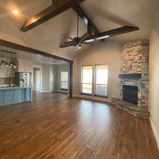 Foto di un grande soggiorno american style aperto con pareti grigie, pavimento in gres porcellanato, camino ad angolo, cornice del camino in pietra e pavimento marrone