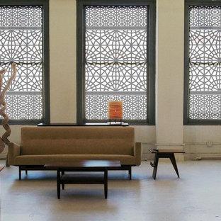 Trendy concrete floor living room photo in Other with beige walls
