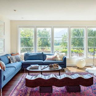 Foto di un grande soggiorno minimalista aperto con pareti beige, pavimento in legno massello medio, pavimento marrone e nessun camino