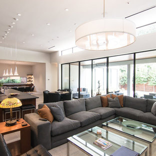 ダラスの大きいミッドセンチュリースタイルのおしゃれなLDK (ライブラリー、白い壁、磁器タイルの床、横長型暖炉、石材の暖炉まわり、埋込式メディアウォール、ベージュの床) の写真