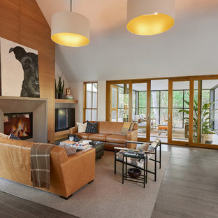 Inspiration for a large contemporary open concept gray floor and medium tone wood floor living room remodel in Grand Rapids with white walls, a standard fireplace, a concrete fireplace and a tv stand