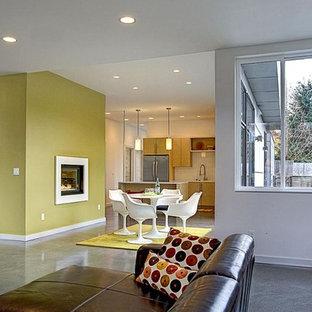 シアトルの中サイズのコンテンポラリースタイルのおしゃれなLDK (マルチカラーの壁、コンクリートの床、標準型暖炉、漆喰の暖炉まわり、テレビなし) の写真