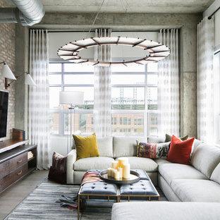 デンバーの中サイズのインダストリアルスタイルのおしゃれなリビングロフト (無垢フローリング、暖炉なし、壁掛け型テレビ、グレーの床、白い壁) の写真