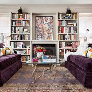 Imagen de biblioteca en casa cerrada, clásica renovada, de tamaño medio, sin televisor, con paredes grises, suelo de madera en tonos medios, chimenea tradicional, marco de chimenea de madera y suelo violeta