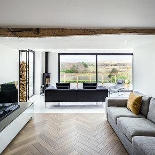 Diseño de salón actual, de tamaño medio, con paredes blancas, suelo de madera en tonos medios, estufa de leña, televisor independiente y suelo beige