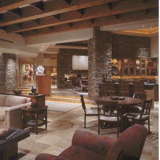 Exemple d'un très grand salon sud-ouest américain ouvert avec un bar de salon, un mur beige, un sol en calcaire, une cheminée standard, un manteau de cheminée en pierre et un téléviseur dissimulé.