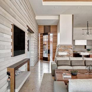 Esempio di un grande soggiorno chic aperto con pareti beige, pavimento in pietra calcarea, cornice del camino in pietra, TV a parete e pavimento beige