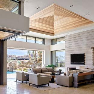 Aménagement d'un grand salon sud-ouest américain ouvert avec un mur beige, un sol en calcaire, un manteau de cheminée en pierre, un téléviseur fixé au mur et un sol beige.