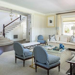 ニューヨークの広いトラディショナルスタイルのおしゃれな独立型リビング (フォーマル、ベージュの壁、濃色無垢フローリング、コーナー設置型暖炉、コンクリートの暖炉まわり、テレビなし、茶色い床) の写真