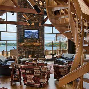 This is an example of a large rustic formal open plan living room in Other with light hardwood flooring, a standard fireplace, a stone fireplace surround, a wall mounted tv and brown walls.