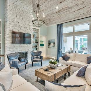 他の地域のビーチスタイルのおしゃれなリビング (青い壁、無垢フローリング、標準型暖炉、石材の暖炉まわり、壁掛け型テレビ、茶色い床) の写真