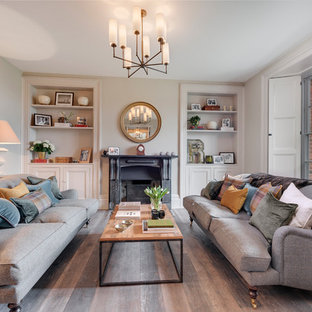 Inspiration for a large country formal enclosed living room in Devon with grey walls, dark hardwood flooring, a stone fireplace surround, a wall mounted tv, brown floors and a standard fireplace.