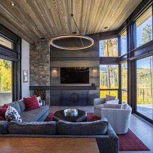 Diseño de salón para visitas cerrado, industrial, con suelo de cemento, chimenea tradicional, marco de chimenea de metal, paredes blancas, televisor colgado en la pared y suelo gris