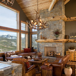 Exemple d'un salon montagne avec un mur vert, un sol en bois brun, une cheminée standard, un manteau de cheminée en pierre et aucun téléviseur.