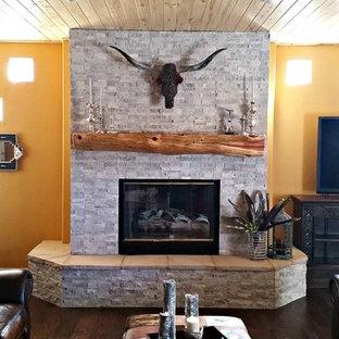 Idées déco pour un salon sud-ouest américain avec un mur jaune, un sol en bois foncé et un manteau de cheminée en pierre.
