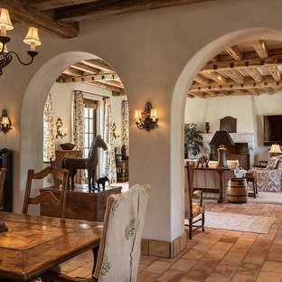 Photo of a large country formal open concept living room in Phoenix with beige walls, terra-cotta floors, a standard fireplace, a stone fireplace surround and a wall-mounted tv.