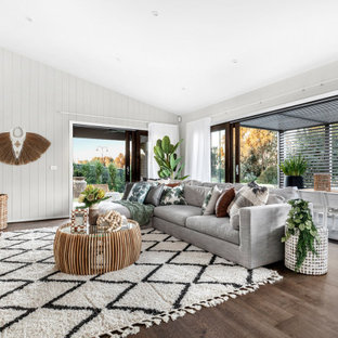 Beach style living room in Other with white walls, medium hardwood floors and brown floor.