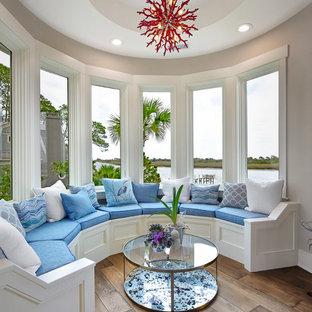 Coastal medium tone wood floor and brown floor living room photo in Charleston with beige walls
