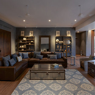 This is an example of a large contemporary living room in Ahmedabad with grey walls and dark hardwood flooring.