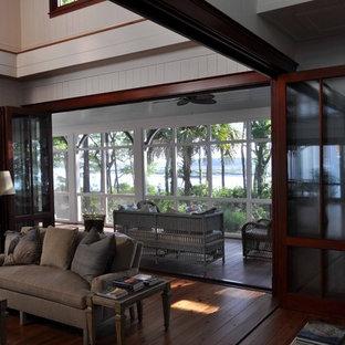 Foto di un grande soggiorno classico aperto con pareti bianche, pavimento in legno massello medio, cornice del camino in mattoni e camino classico