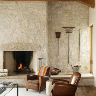 オースティンの中サイズのおしゃれなLDK (フォーマル、マルチカラーの壁、無垢フローリング、標準型暖炉、石材の暖炉まわり、埋込式メディアウォール) の写真