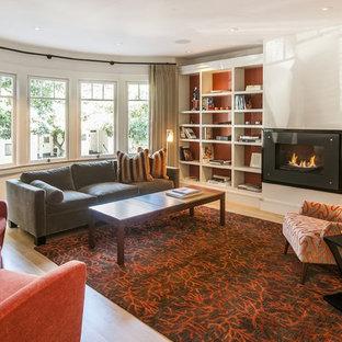 Esempio di un grande soggiorno design chiuso con sala formale, pareti arancioni, parquet chiaro, camino lineare Ribbon, cornice del camino in intonaco e nessuna TV