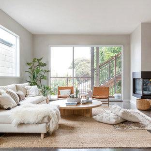 На фото: большая открытая гостиная комната в скандинавском стиле с серыми стенами, темным паркетным полом, угловым камином, фасадом камина из металла и коричневым полом без ТВ с