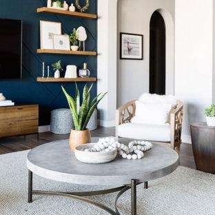 Diseño de salón abierto, ecléctico, de tamaño medio, con paredes azules, televisor colgado en la pared y suelo marrón