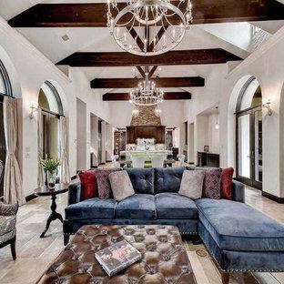 Ispirazione per un ampio soggiorno mediterraneo aperto con pareti bianche, pavimento in travertino e cornice del camino in pietra