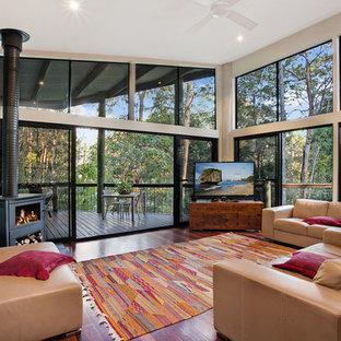 Modelo de salón contemporáneo con paredes blancas, suelo de madera oscura, estufa de leña y televisor independiente