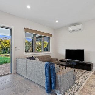 Diseño de salón minimalista, pequeño, con paredes blancas, suelo de travertino y televisor independiente