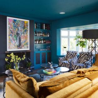 ロンドンのエクレクティックスタイルのおしゃれな独立型リビング (フォーマル、青い壁、濃色無垢フローリング、標準型暖炉、タイルの暖炉まわり、壁掛け型テレビ、茶色い床) の写真
