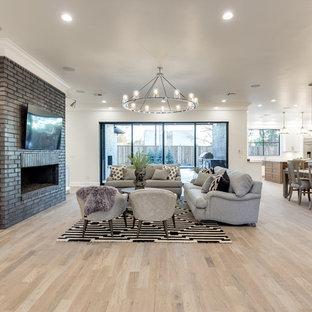 Immagine di un ampio soggiorno chic aperto con sala formale, pareti bianche, pavimento in legno massello medio, camino classico, cornice del camino in mattoni e TV a parete
