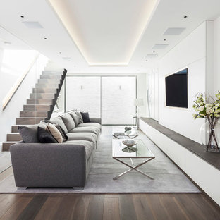 This is an example of a large contemporary formal open plan living room in London with white walls, medium hardwood flooring, no fireplace and a wall mounted tv.