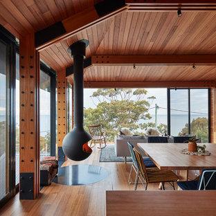 Exempel på ett modernt allrum med öppen planlösning, med bruna väggar, mellanmörkt trägolv, en hängande öppen spis, en väggmonterad TV och brunt golv