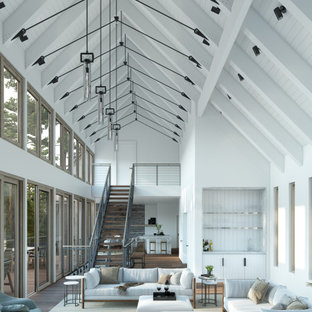 Imagen de salón abierto, contemporáneo, grande, con paredes blancas, suelo de madera en tonos medios, chimenea de esquina y suelo marrón