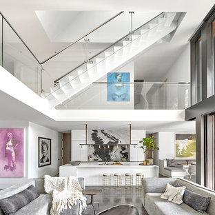 Ispirazione per un grande soggiorno contemporaneo aperto con pareti bianche, pavimento in cemento, camino sospeso, cornice del camino in legno, TV nascosta e pavimento grigio