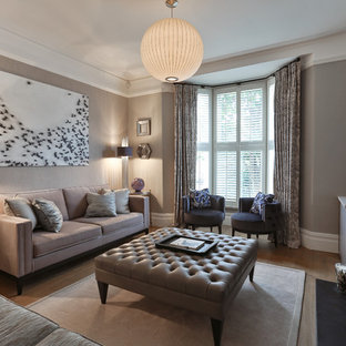 Design ideas for a medium sized modern formal enclosed living room in London with grey walls, light hardwood flooring, a standard fireplace, a stone fireplace surround and a freestanding tv.