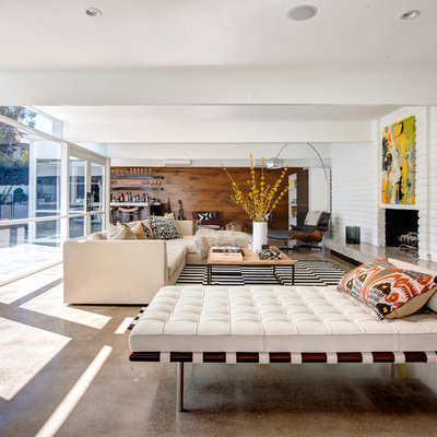 Inspiration for a large contemporary open concept concrete floor and brown floor living room remodel in Orange County with white walls, a standard fireplace, a brick fireplace and no tv