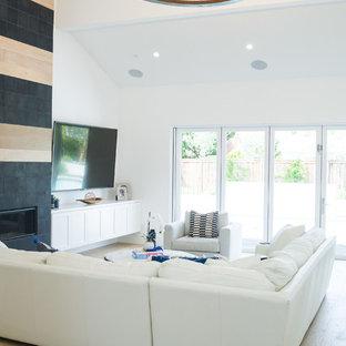 オレンジカウンティの大きいコンテンポラリースタイルのおしゃれなLDK (黄色い壁、淡色無垢フローリング、標準型暖炉、タイルの暖炉まわり、壁掛け型テレビ、白い床) の写真