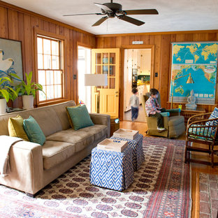 Example of a mid-sized eclectic enclosed medium tone wood floor living room design in Richmond with a standard fireplace and a wall-mounted tv