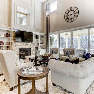 Geräumiges, Offenes Wohnzimmer mit weißer Wandfarbe, braunem Holzboden, Kamin, Kaminumrandung aus gestapelten Steinen, Multimediawand, freigelegten Dachbalken und Wandpaneelen in Charlotte
