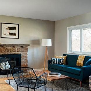 フィラデルフィアの中サイズのミッドセンチュリースタイルのおしゃれなLDK (グレーの壁、淡色無垢フローリング、標準型暖炉、石材の暖炉まわり、テレビなし) の写真