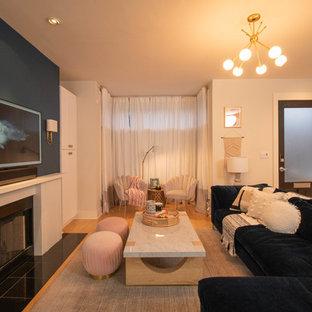 Ejemplo de salón abierto, contemporáneo, grande, con paredes azules, suelo de madera clara, chimenea tradicional, marco de chimenea de madera, televisor colgado en la pared y suelo amarillo