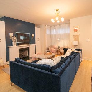Idee per un grande soggiorno design aperto con pareti blu, parquet chiaro, camino classico, cornice del camino in legno, TV a parete e pavimento giallo
