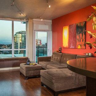 Foto de salón abierto, contemporáneo, pequeño, con parades naranjas, suelo de madera en tonos medios, chimenea tradicional, marco de chimenea de piedra y televisor colgado en la pared