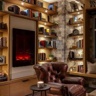 ラスベガスの中サイズのインダストリアルスタイルのおしゃれな独立型リビング (ライブラリー、白い壁、クッションフロア、吊り下げ式暖炉、木材の暖炉まわり、テレビなし、茶色い床) の写真