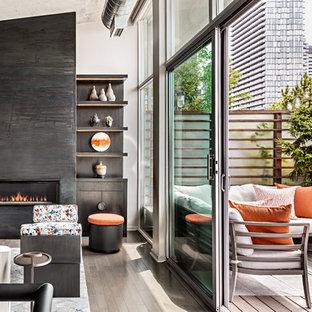 Idee per un piccolo soggiorno design aperto con sala formale, pareti grigie, pavimento in legno massello medio, camino sospeso, cornice del camino in metallo, TV nascosta e pavimento grigio