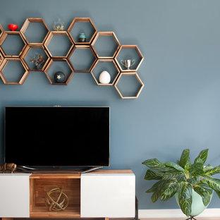 Modelo de salón abierto, minimalista, de tamaño medio, sin chimenea, con paredes azules, televisor independiente y suelo de madera clara